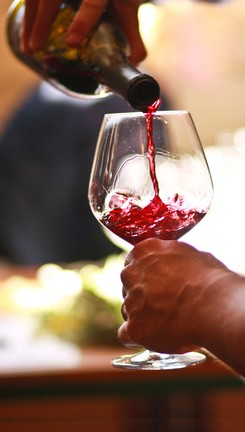 bottle of pinot noir being poured into a glass